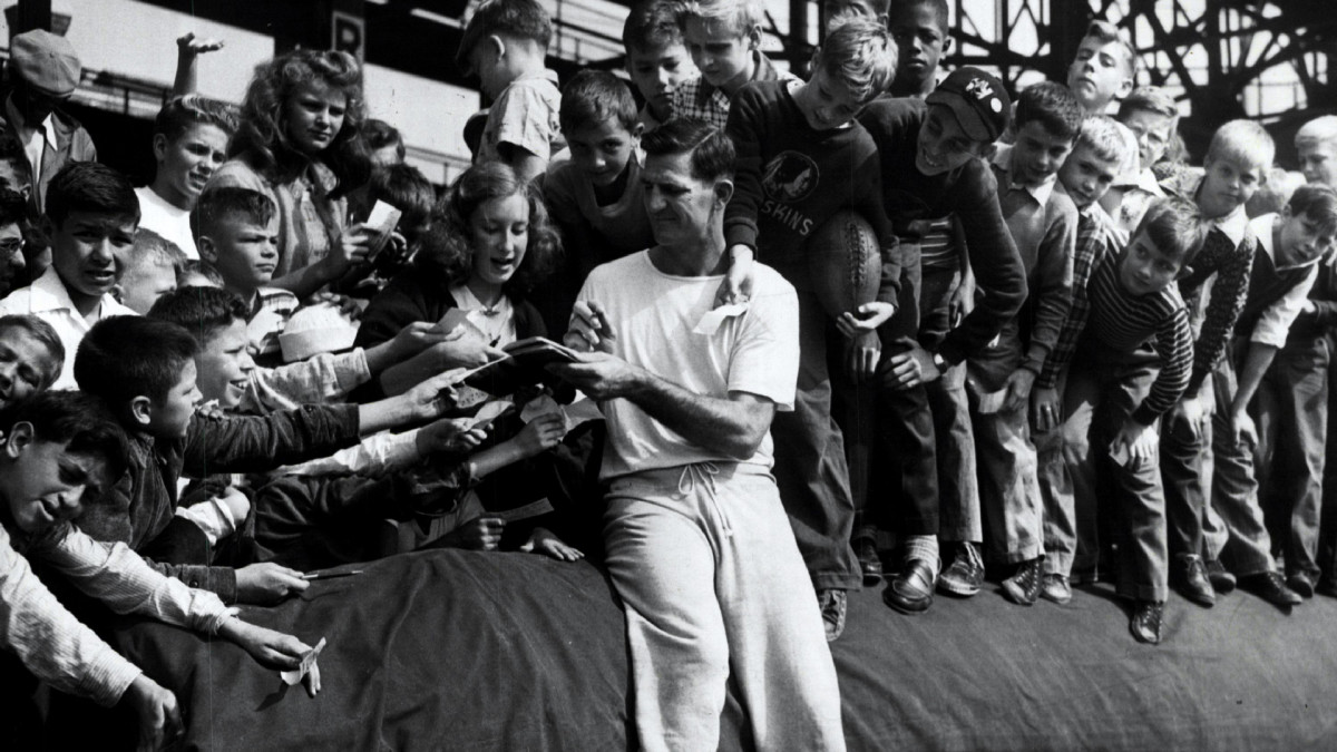 Washington's Sammy Baugh signed autographs for fans during a late 1940s practice.