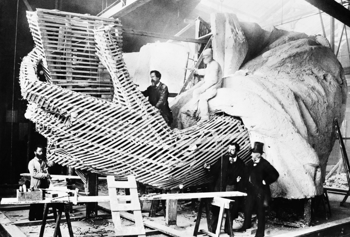Frédéric-Auguste Bartholdi, creator of the Statue of Liberty, explains the inner construction of the hand section of the statue to a visitor, c. 1872.