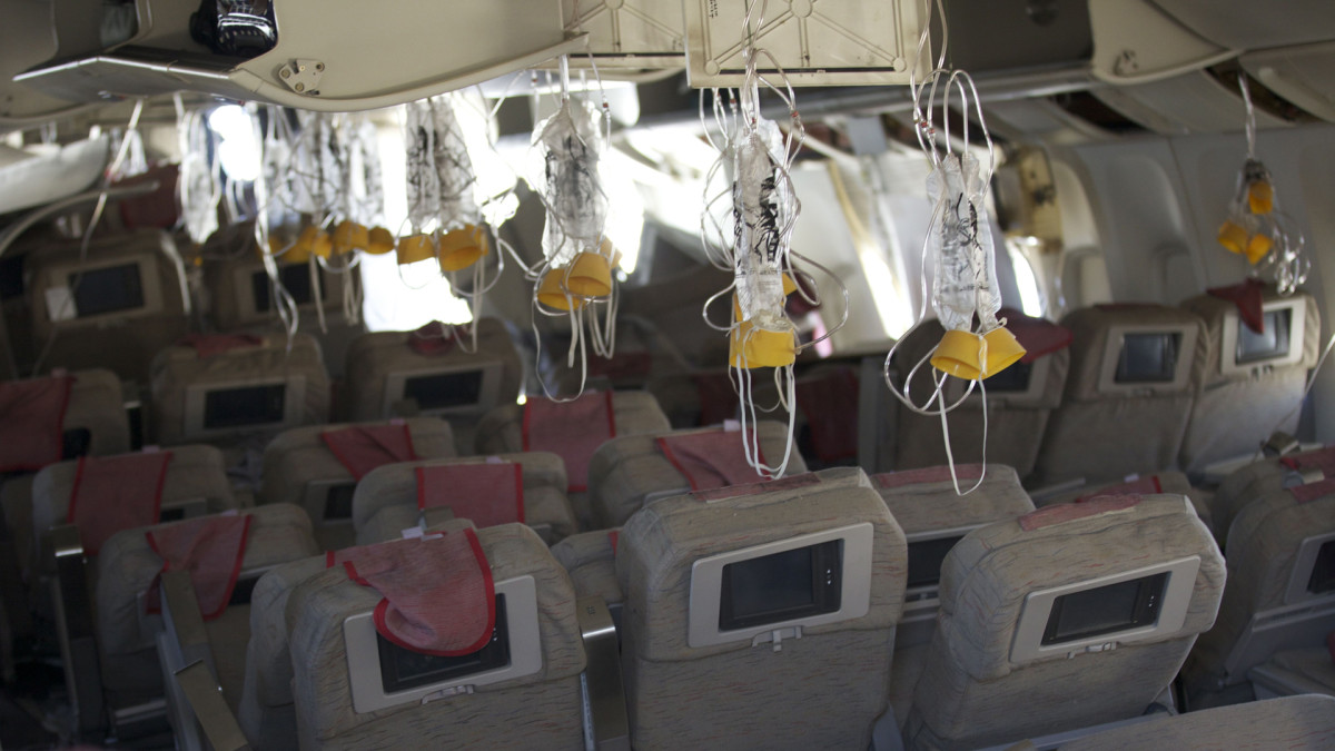 Oxygen masks hang from the ceiling in the cabin interior of Asiana Airlines flight 214 following a crash on July 6, 2013 in San Francisco, California. The Boeing 777 passenger aircraft from Asiana Airlines coming from Seoul, South Korea crash-landed on the runway at San Francisco International Airport.