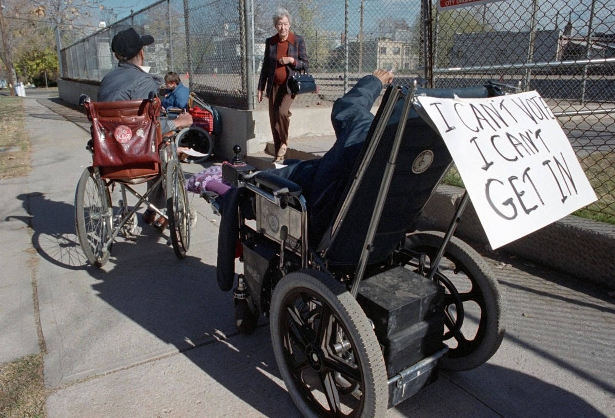 Wheelchair bound protesters surround an entrance to a Denver polling place to draw attention to the flights of stairs that make it impossible to them to reach to voting booths, c. 1988.