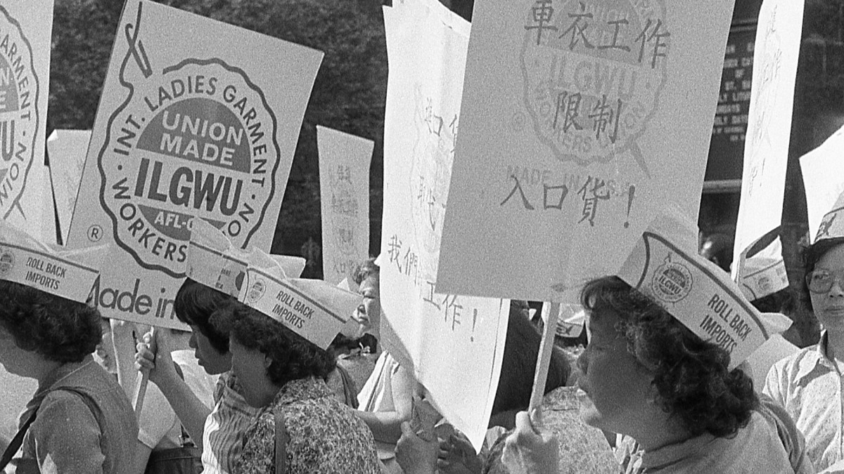 Women garment workers with the ILGWU stand on the streets of Chinatown with protest signs in hand.