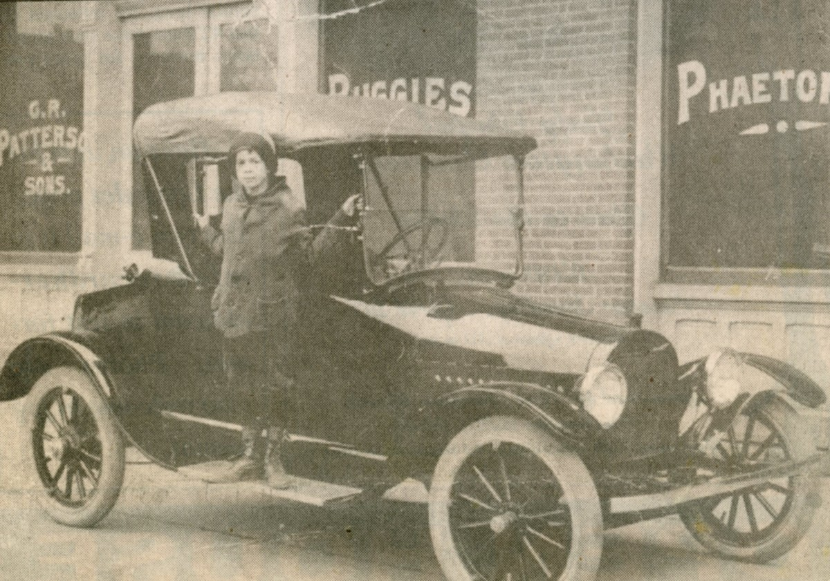 Photograph of Postell Patterson, son of F. D. Patterson, on the running board of a Greenfield-Patterson Roadster as introduced in 1915. The Patterson showroom is in the background.