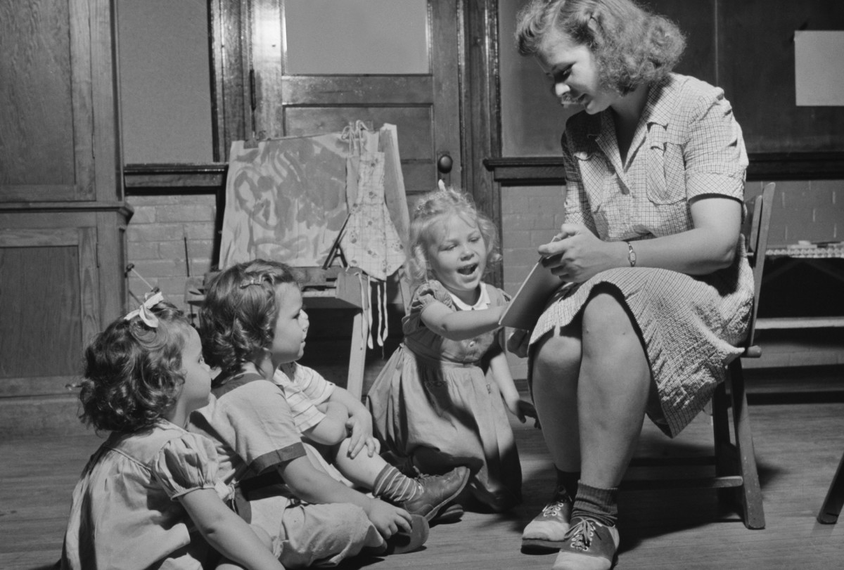 A woman reading a story to three young children at a Child Care Center in New Britain, Connecticut. Photographed by Gordon Parks for Office of War Information, June 1943.
