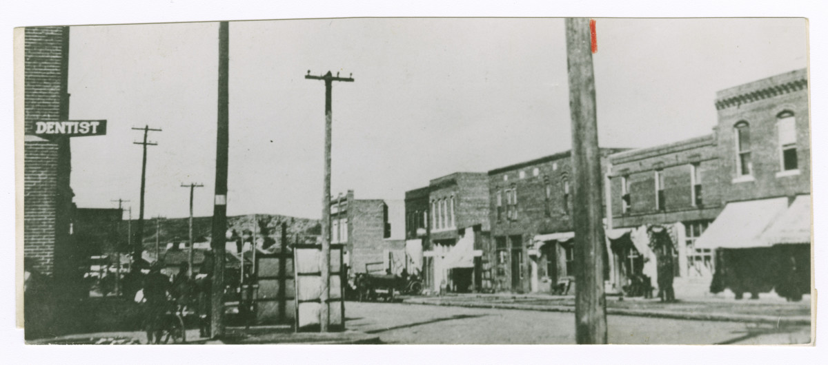 A black-and-white photograph of the Greenwood district in Tulsa, Oklahoma, before 1921. Depicted are storefronts, telephone wires and a sign for a dentist's office.