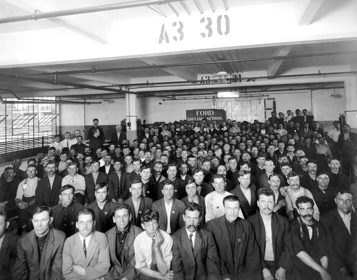 Immigrants working at the Ford Motor Company attending classes after work at the factory to learn the English language, in Detroit, Michigan, late 1900s or early 1910s. The classes were sponsored by the Detroit YMCA.