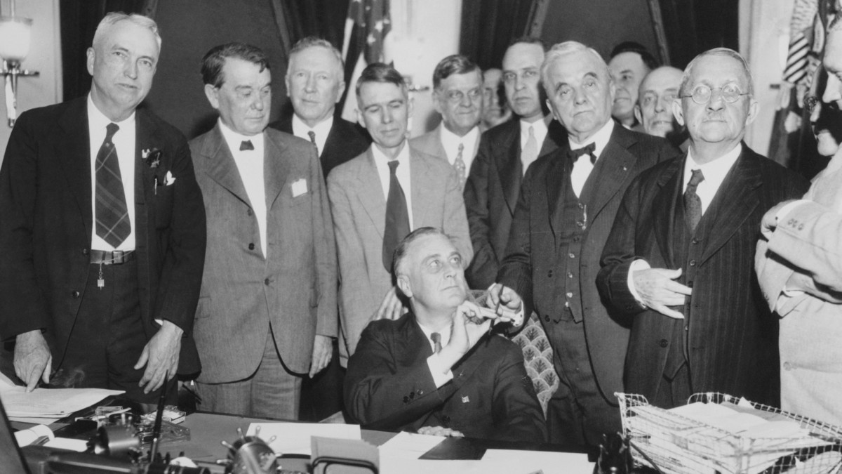 May 1933: President Roosevelt presents Senator Norris of Nebraska with the pen he used in signing the Muscle Shoals Bill. Sponsored by the Nebraska senator, the bill provided for development of the entire Tennessee Valley,