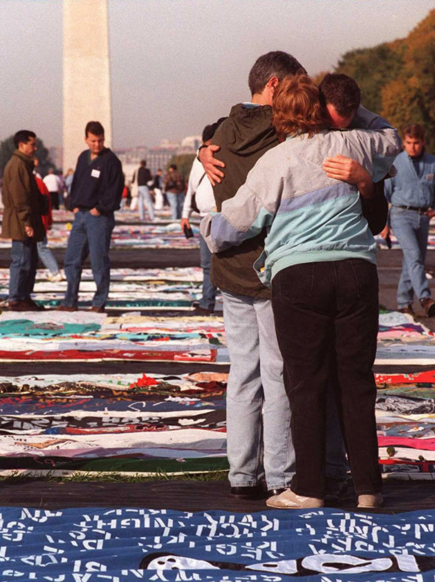 Three people comfort each other while thousands of friends and family members of AIDS victims visit the AIDS Memorial Quilt displayed on the National Mall,Washington, D.C.,October 12, 1996.