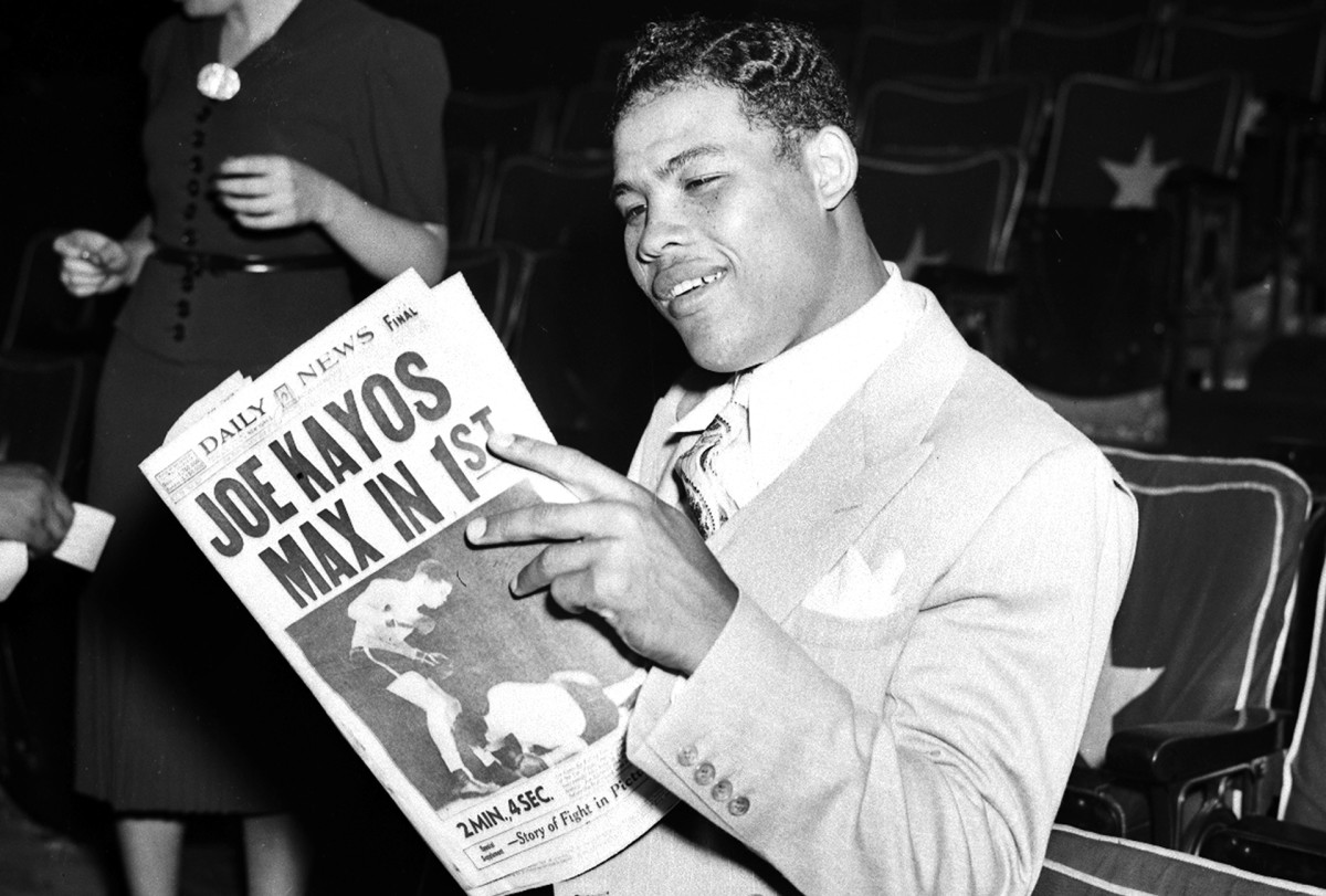 Joe Louis smiles as he reads the NY Daily News the day after his fight against Schmeling on June 22, 1938.