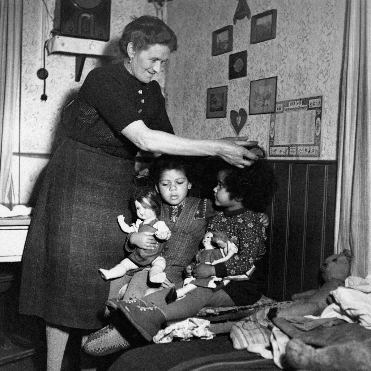 A German woman taking care of two mixed-race German children, c. 1950s.