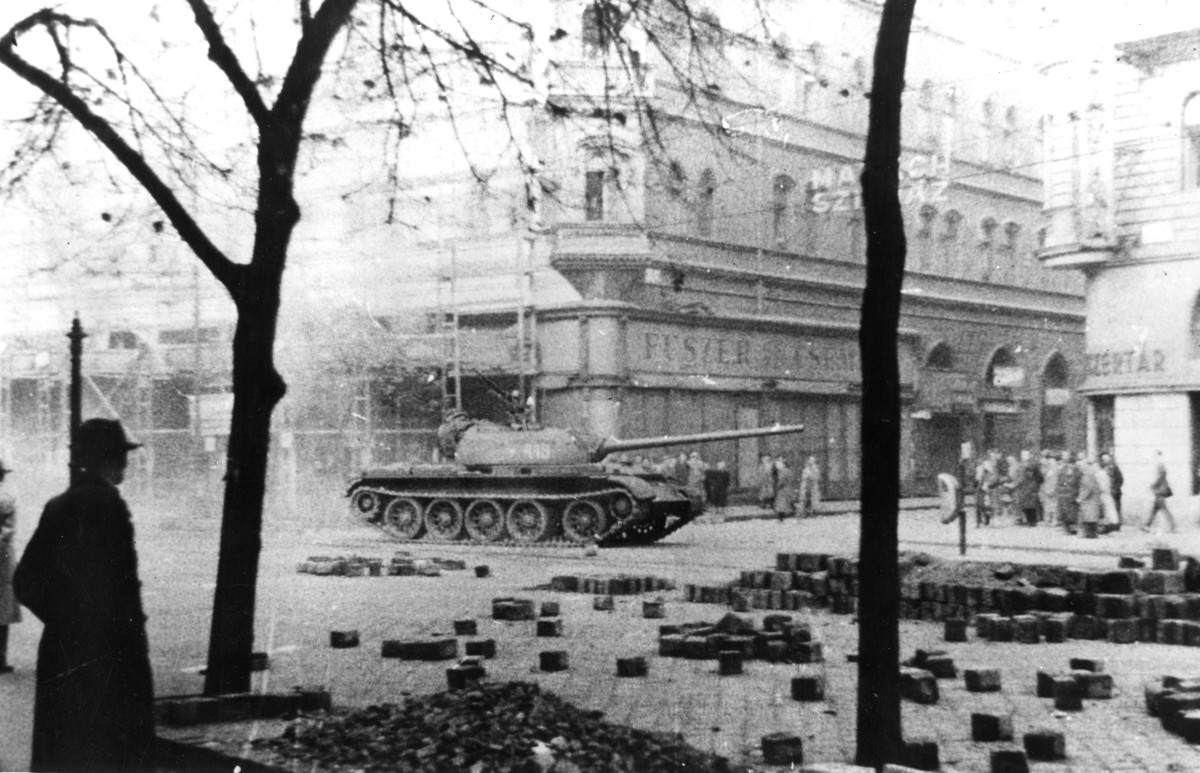 View of Russian Army tank as it patrols past pedestrians during the Hungarian Revolution, Budapest, Hungary, November 1956.