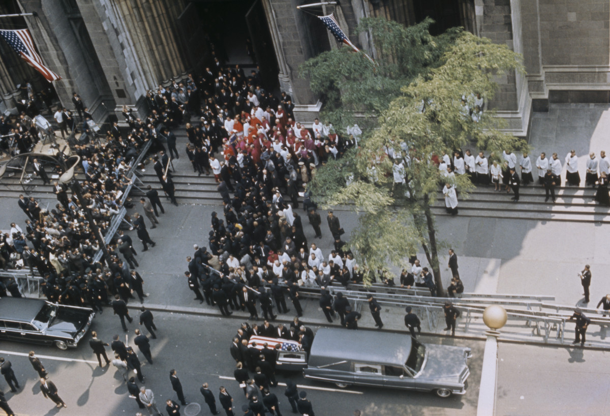 View of mourners and members of the congregation exiting through the doors of Saint Patrick's Cathedral, New York as they follow the coffin containing the body of the assassinated Senator Robert F. Kennedy after the funeral and requiem mass on June 8, 1968. The coffin, being loaded into the back of a hearse, would be transported from New York to Washington, D.C. by a special train for burial in Arlington National Cemetery.