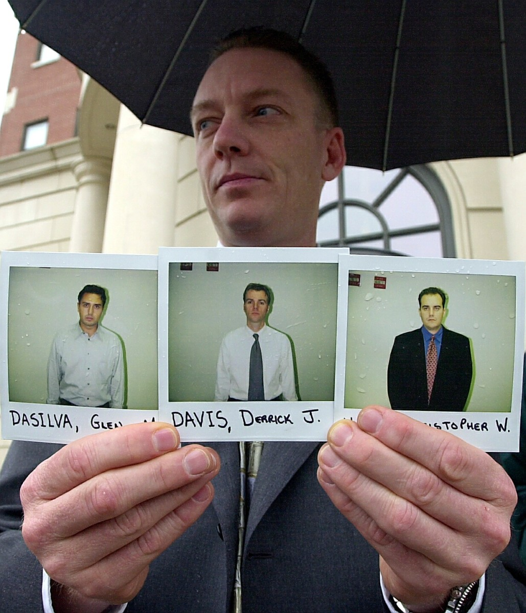 Lt. Robert Patnaude of the New York State Police Special Investigation Unit holds mugshots of Glen DaSilva, Derrick Davis and Christopher Harn outside the Federal Courthouse in White Plains, New York on November 12, 2002