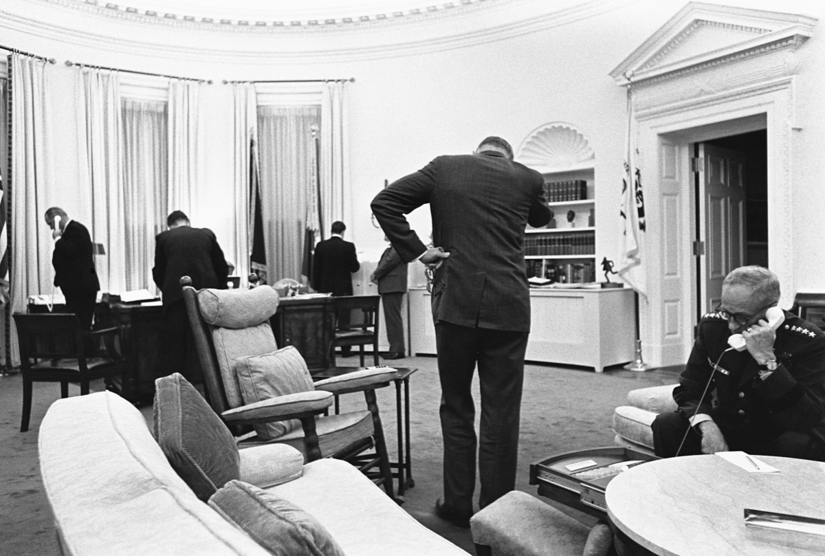 President Lyndon B. Johnson and his advisers gather in the Oval Office to communicate with Federal troops sent in to quell race riots in Detroit, and to plan their handling of the crisis. 1967.