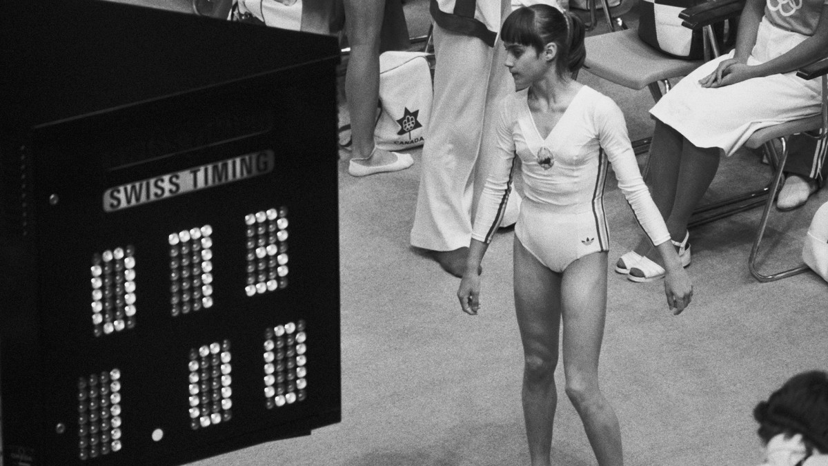 Nadia Comaneci looks at the Olympic scoreboard indicating her perfect score of 10.0, as 1.00 because the computer and the display facility were not equipped to handle what Nadia was going to do to the Olympic gymnastics competition.