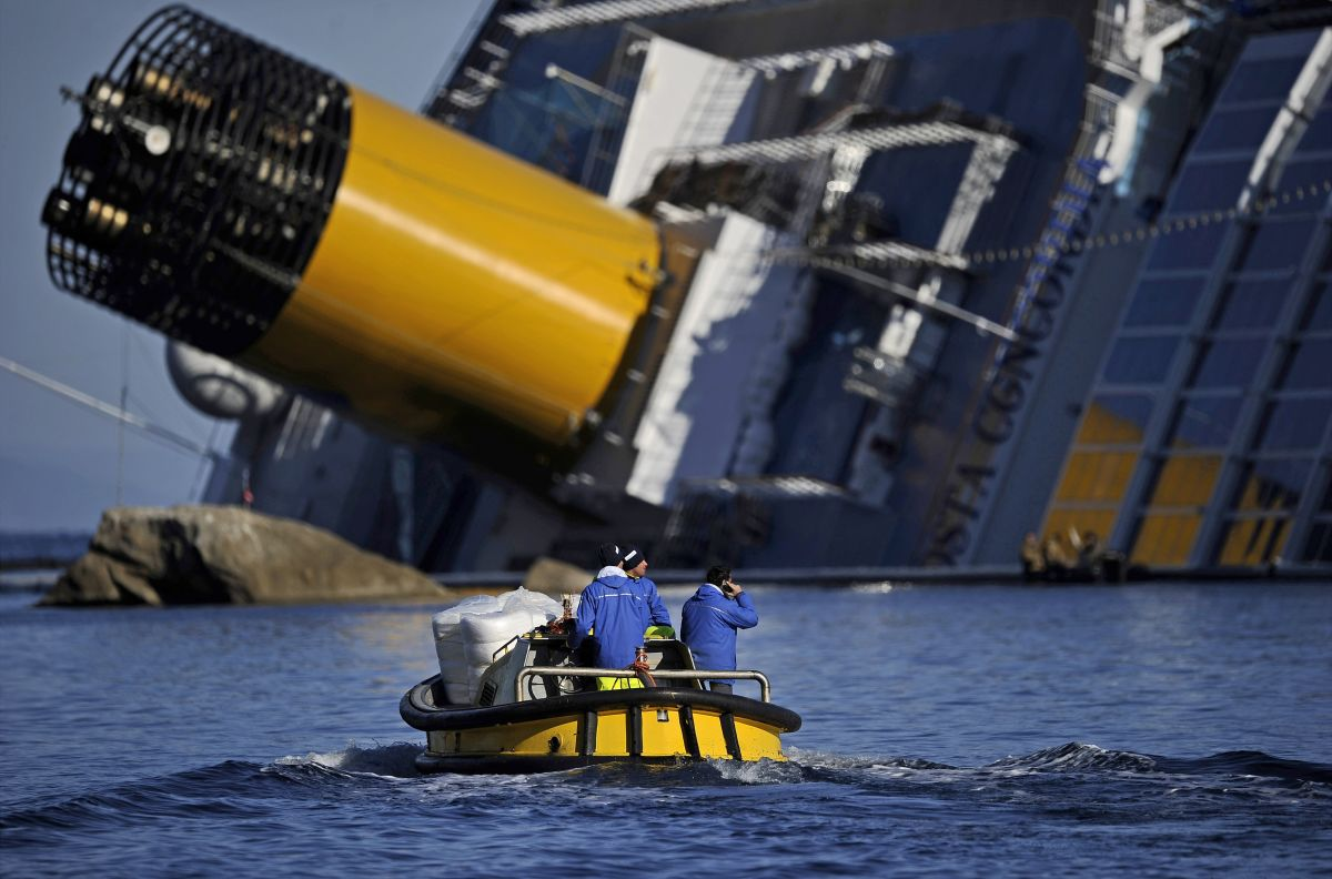 Technicians pass in a small boat near the stricken cruise liner Costa Concordia lying aground in front of the Isola del Giglio on January 26, 2012 after hitting underwater rocks on January 13.
