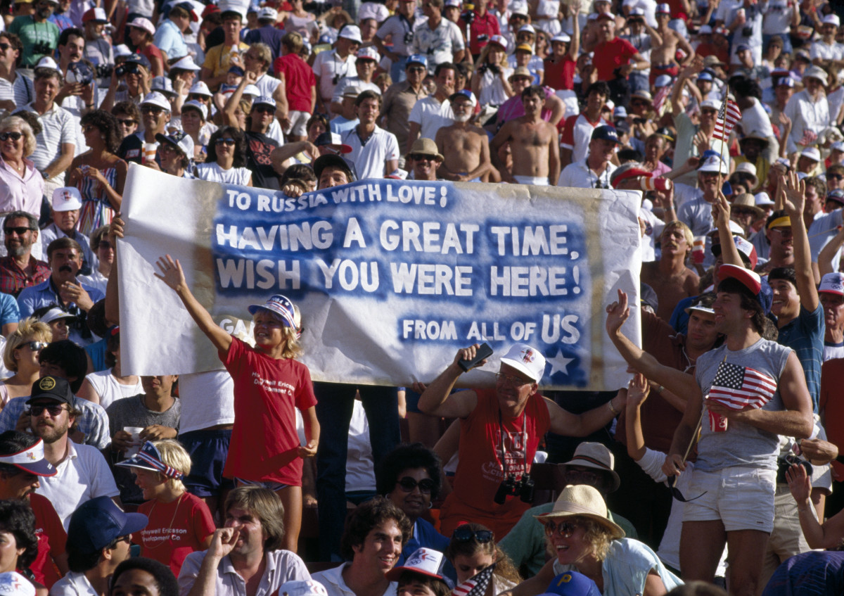 American sports fans display a banner with the message 'To Russia With Love! Having a Great Time, Wish You Were Here,' in reference to the boycott of the Games by the Soviet Union and 13 other Eastern Bloc countries, inside the Memorial Coliseum during the 1984 Summer Olympics in Los Angeles.