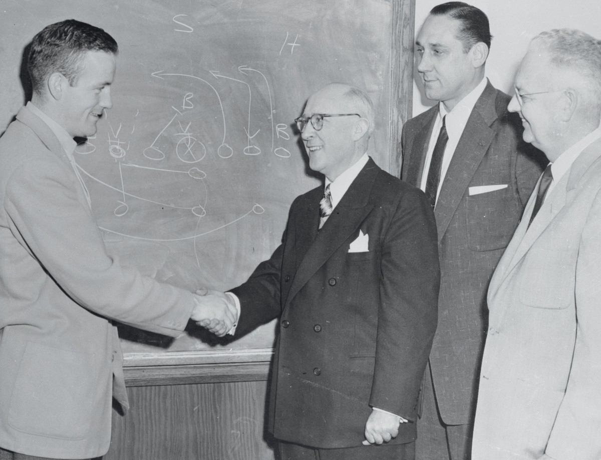 """Notre Dame coach Terry Brennan, left, named """"Coach of the Week,"""" is congratulated by (L-R): Arch Ward, Sports Editor, Chicago Tribune; Ed Krause, Notre Dame's Director of Athletics; and Herb Jones, Business Manager of Athletics."""