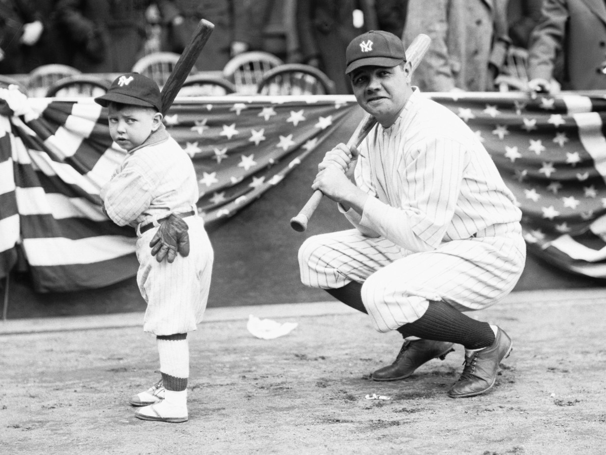 Babe Ruth on the field with moppet batter by his side.