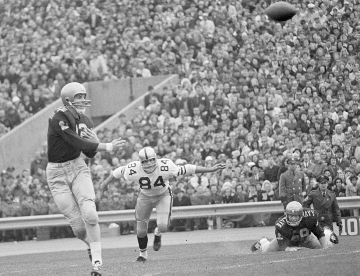Original Caption) 11/28/1964-Philadelphia, Pennsylvania- Roger Staubach, (12), just gets off his pass to halfback Tom Leiser just in time as Army end Tom Schwartz, (84), barrels down on the Middle, past guard Gene Hardman, (on ground). Staubach was rushed by the Cadets early in the second quarter to give Army a 2-0 lead on a safety.