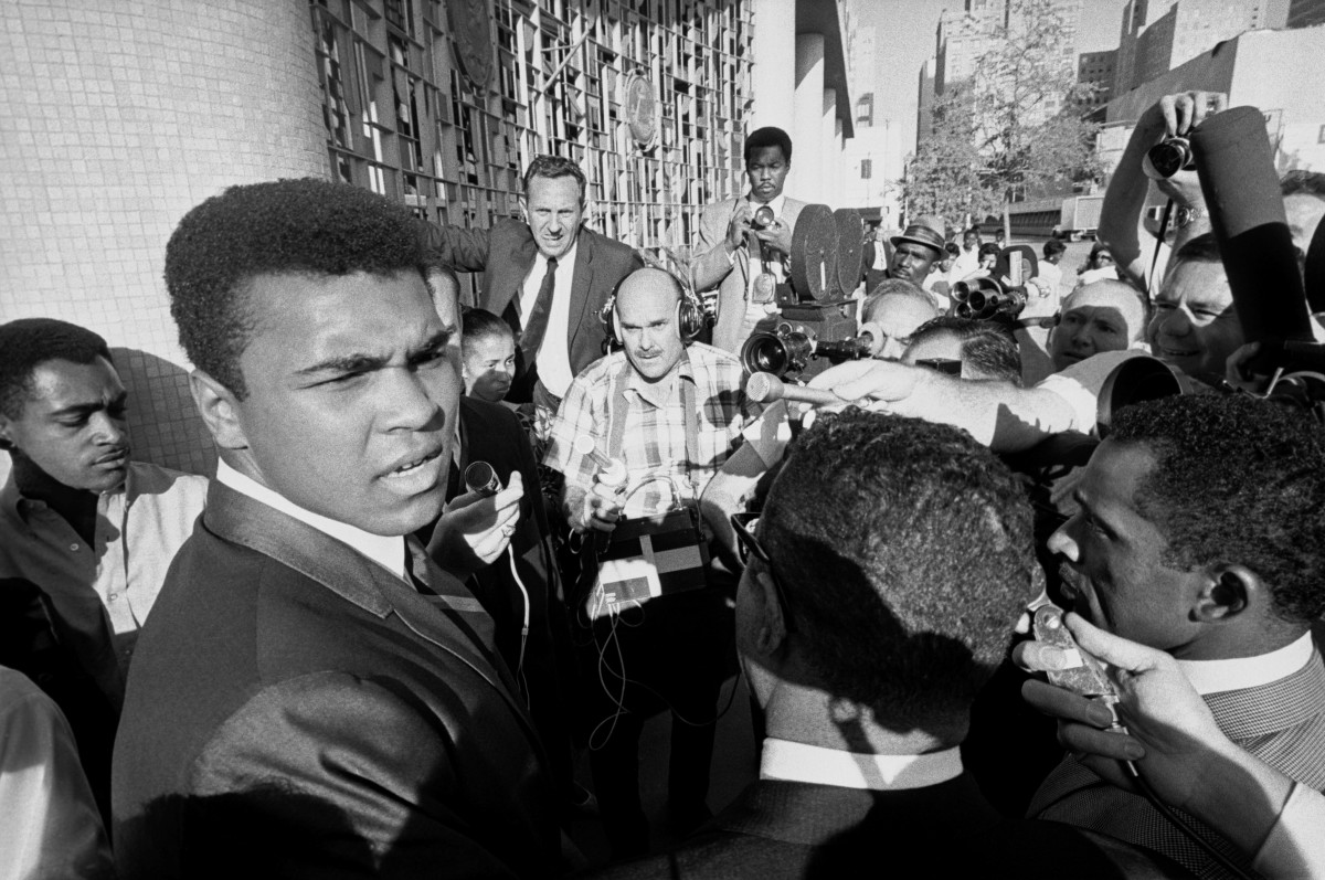 Former world heavyweight boxing champion Muhammad Ali (L) is surrounded by journalists as he leaves the federal court after a jury found him guilty on charges of refusing to be inducted into the U.S. armed forces. Clay contended that he was a Nation of Islam minister and not subject to the draft.