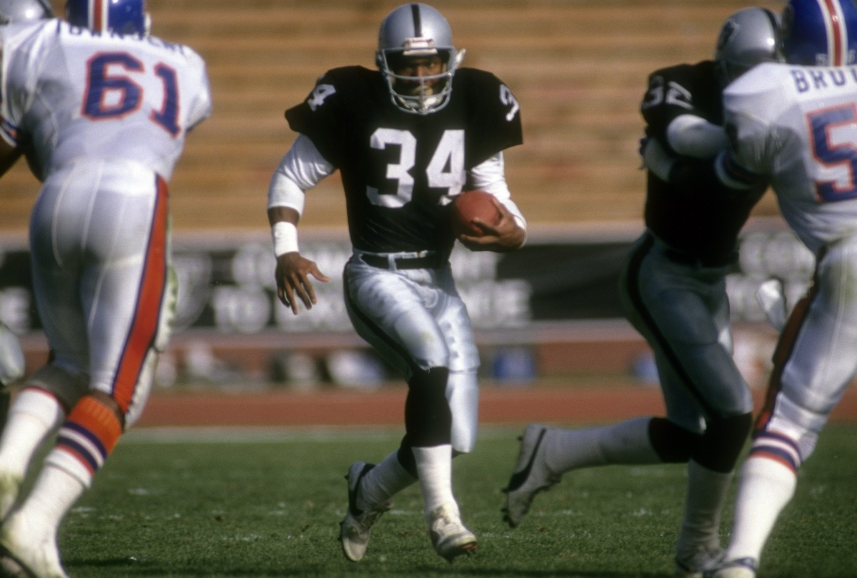 LOS ANGELES, CA - DECEMBER 1989: Running back Bo Jackson #34 of the Los Angeles Raiders in action carries the ball against the Denver Broncos December 3, 1989 during an NFL game at the Los Angeles Coliseum in Los Angeles, California. Jackson played for the Raiders from 1987-90. (Photo by Focus on Sport/Getty Images)