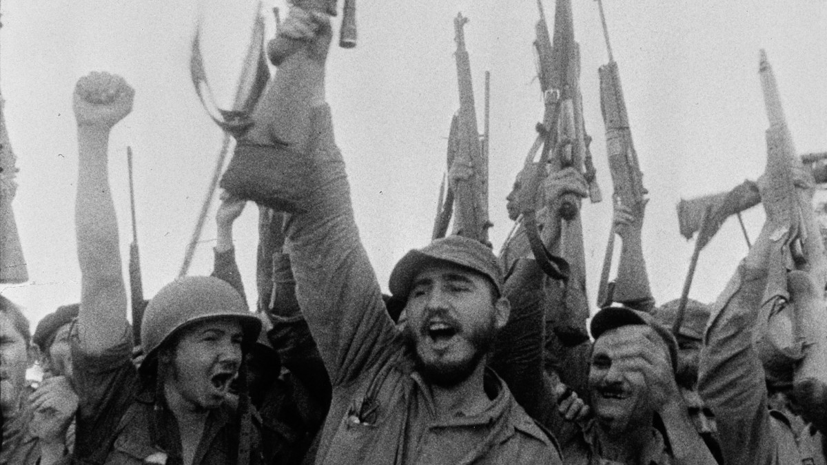 Cuban guerilla leader and future dictator Fidel Castro and associates as they cheer and raise their weapons and fists in the air on the CBS News Special Event 'Rebels of the Sierra Maestra,' Cuba, 1957. (Photo by CBS Photo Archive/Getty Images)