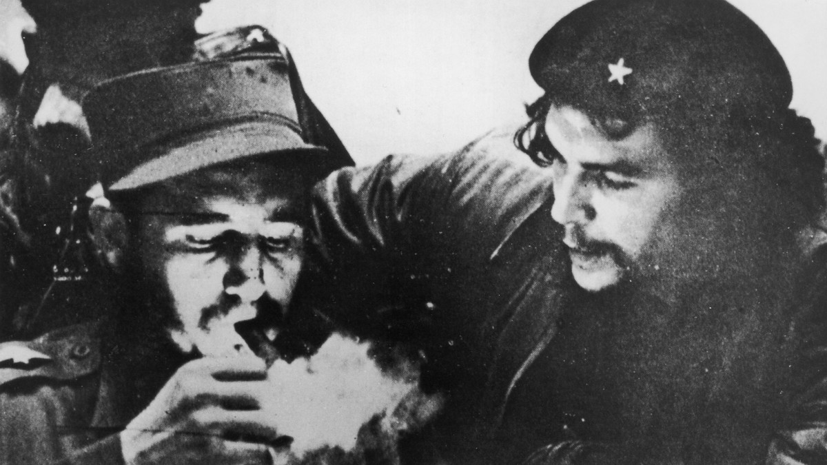 Cuban revolutionary Fidel Castro (left) lights his cigar while Argentine revolutionary Che Guevara (1928-1967) looks on in the early days of their guerrilla campaign in the Sierra Maestra Mountains of Cuba, circa 1956. Castro wears a military uniform while Guevara wears fatigues and a beret.
