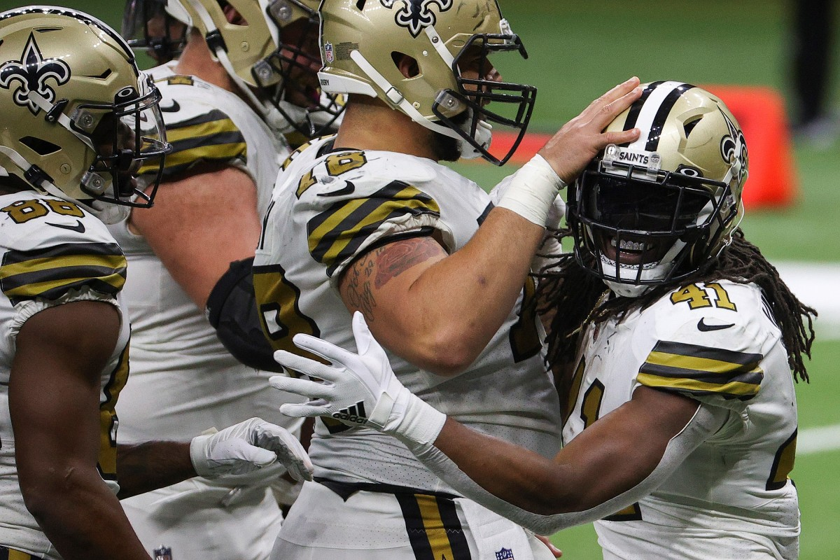 New Orleans Saints teammates congratulate Alvin Kamara after one of his record-tying six touchdowns against the Minnesota Vikings in 2020.
