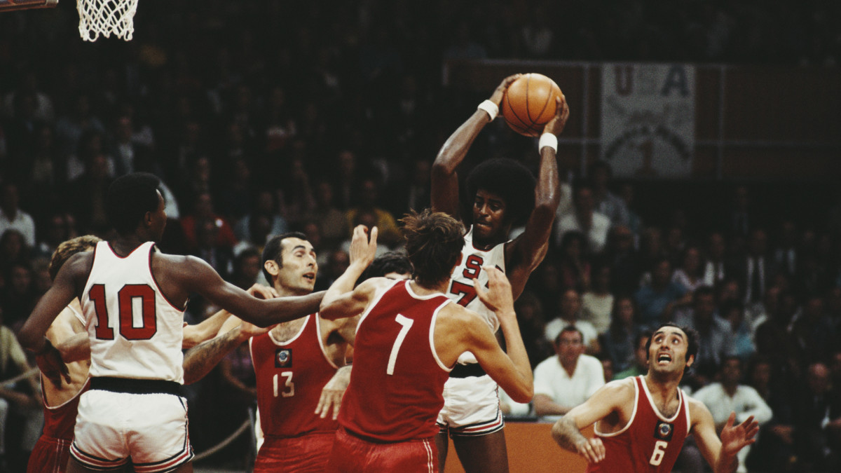 View of action between the Soviet Union (in red) and United States teams (in white), with American Mike Bantom (#7), surrounded by Soviet players, about to shoot during the final of the Basketball event at the 1972 Summer Olympics.